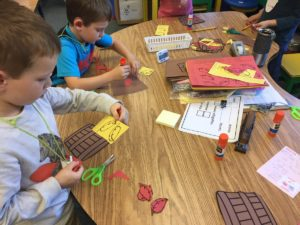 kindergarteners cutting out shapes.
